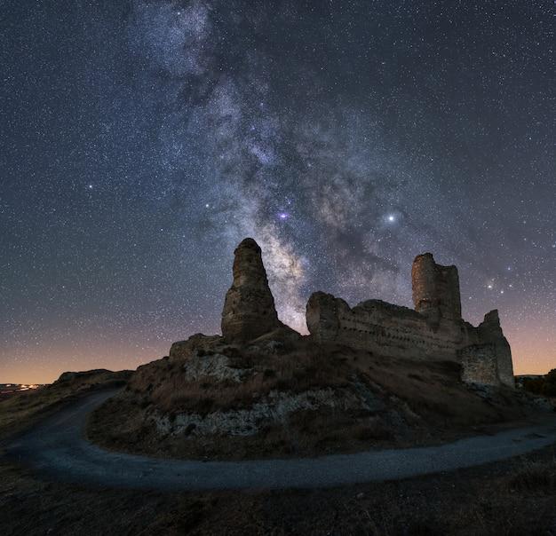 Nachtlandschaft mit der milchstraße über einem alten schloss