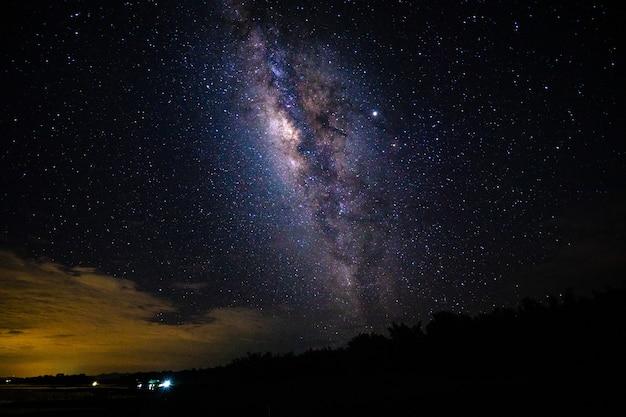 Nachtlandschaft mit der milchstraße und dem licht vom haus an den bergen in thailand