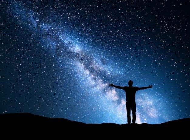Nachtlandschaft mit milchstraße und silhouette eines mannes