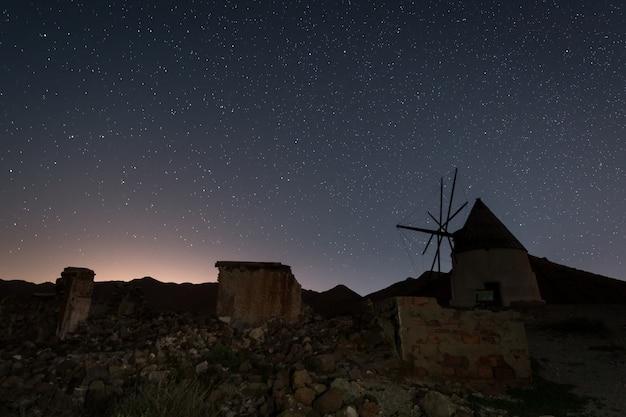Nachtlandschaft mit traditioneller weißer windmühle in san jose. naturpark von cabo de gata. spanien.