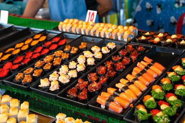 Nachtlebensmittelmarkt in asien. sushi-theken im freien.