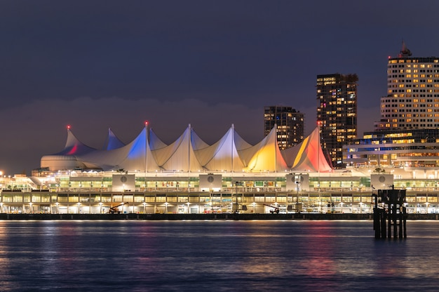 Nachtmarktgebäude und wolkenkratzer, die an der küste in der innenstadt von stanley park, vancouver, kanada leuchten?