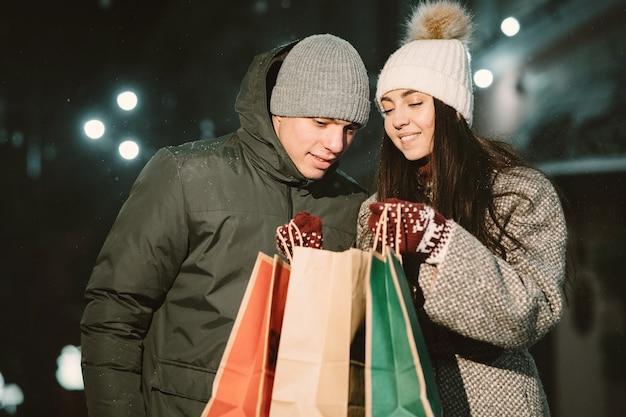 Nachtporträt im freien des jungen paares mit einkaufstaschen