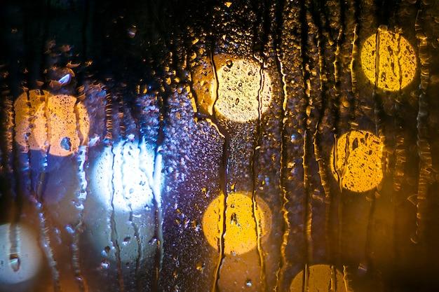 Nachtregen bokeh leuchtet auf der fensterscheibe.