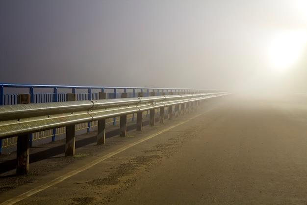 Nachts dichter nebel über leerer straße