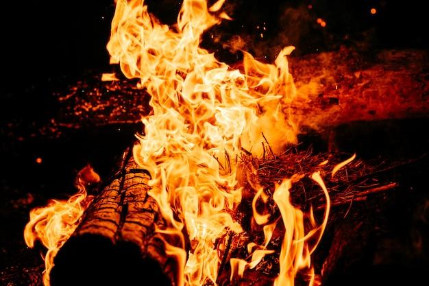 Nachts holz verbrennen. lagerfeuer im touristischen lager in der natur in den bergen.