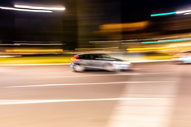 Nachts rollt das auto mit voller geschwindigkeit durch die stadt