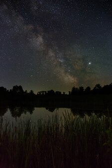 Nachts sterne am himmel. helle milchstraße über dem see.