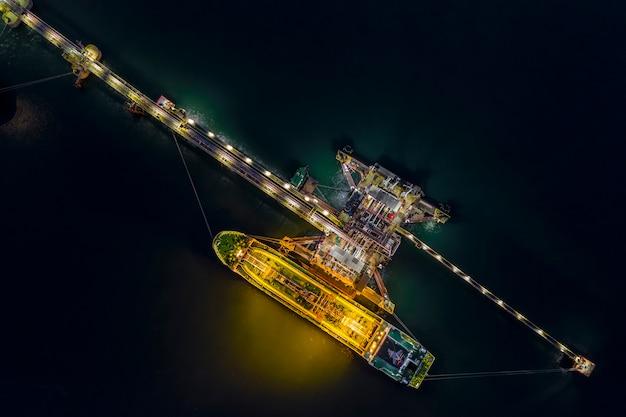 Nachtschussöltanker-versandladen in der draufsicht des ölstationsimport- und -exportlogistik-transportgeschäfts