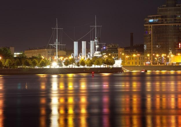 Nachtstadt blick auf den kreuzer aurora am petrogradskaya-damm in den nachtlichtern