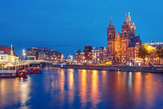 Nachtstadtansicht des amsterdamer kanals, der brücke und der basilika des heiligen nikolaus, holland, niederlande. lange exposition