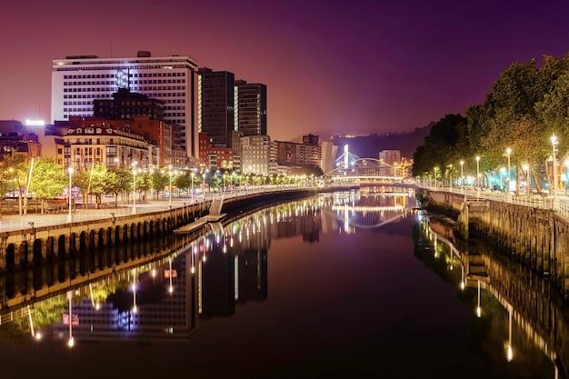 Nachtstadtbild des bilbao baskenlandes spanien mit seinem fluss, brücken und gebäuden.