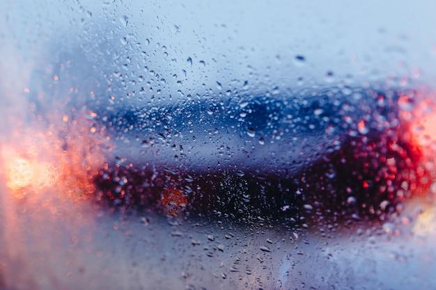 Nachtstadtstraße durch windschutzscheibenautos abstrakter hintergrundwassertropfen auf den glaslichtern und -regen.
