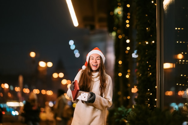 Nachtstraßenporträt der jungen schönen frau, die begeistert handelt. festliche girlandenlichter.