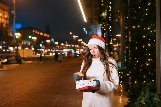 Nachtstraßenporträt der jungen schönen frau, die begeistert handelt