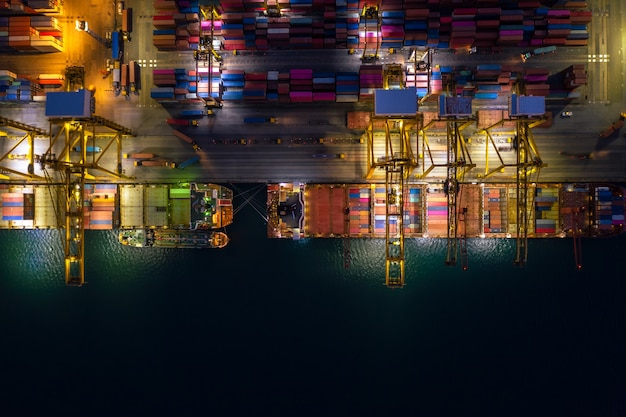Nachtszene be- und entladen von containerschiffen im tiefseehafen luftaufnahme des imports und exports von frachttransporten per containerschiff auf offener see durch den unternehmensdienst und die industriefrachtlogistik