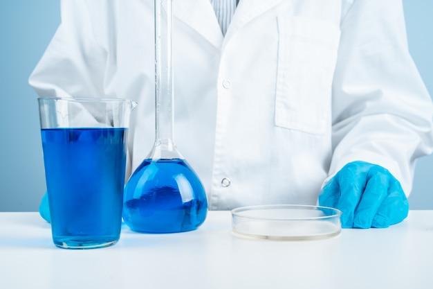 Nachwuchswissenschaftler mit dem reagenzglas, das forschung im klinischen labor macht.