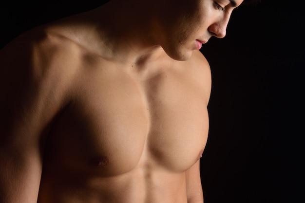 Nackte brust eines mannes auf schwarzem hintergrund