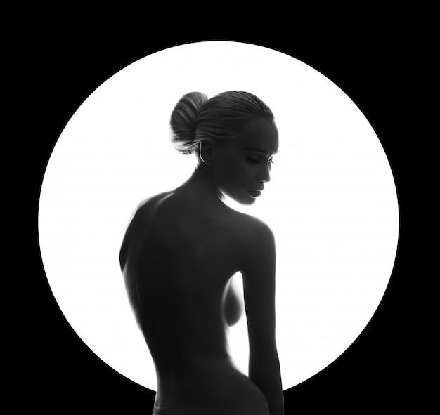 Nackte frau der kunstschönheit auf schwarzem im weißen kreisring. perfekter körper