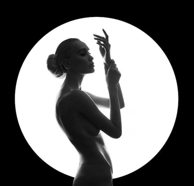 Nackte frau der kunstschönheit auf schwarzer wand im weißen kreisring. perfekter körper, schlanke figur, schöne brüste. nackte modefrau, die perfektes make-up des sinnlichen blickes aufwirft. kunst der erotik