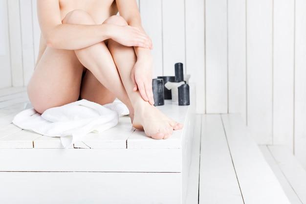 Nackte frau, die am badekurort sitzt