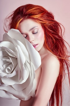 Nackte frau mit roten haaren umarmt eine große papierblume
