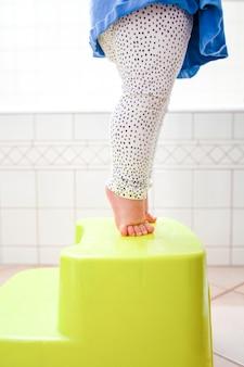 Nackte füße des kleinkindes auf zehenspitzen auf dem hocker