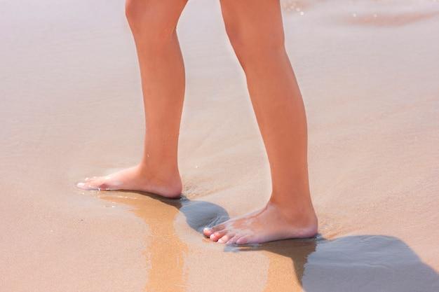 Nackte füße, die am sandigen strand nahe durch das meer gehen