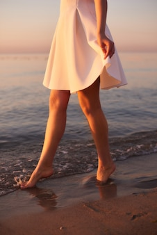 Nackte füße mädchen im weißen kleid im wasser in einem ozeanresort. sommermorgen stimmung, auf dem wasser spazieren