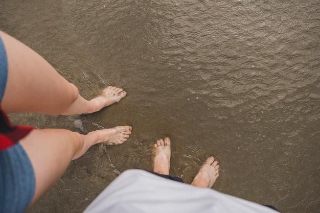 Nackte füße paar auf dem wasser am strand