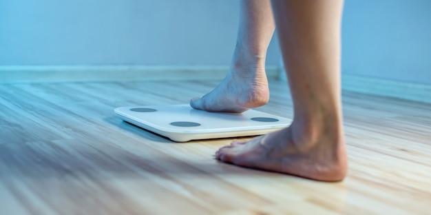 Nackte füße von frauen stehen auf der elektronischen bodenwaage, um das gewicht des körpers zu überprüfen und die zusätzlichen pfunde im blauen licht zu kontrollieren
