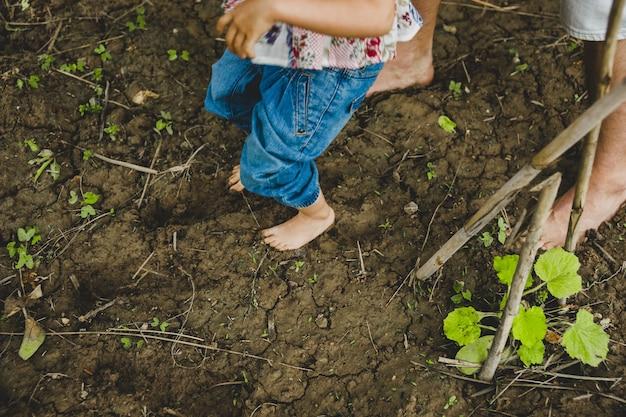 Nackte füße von kindern, die im schlamm spielen