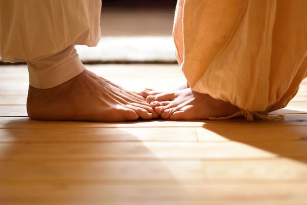 Nackte füße von mann und frau, die mit einem partner tantra yoga praktizieren