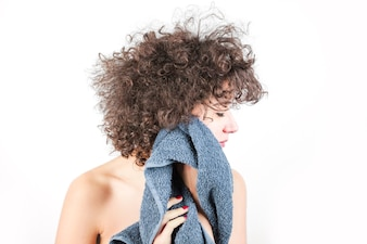 Nackte junge Frau mit dem gelockten Haar wischt ihr Gesicht mit Tuch gegen weißen Hintergrund ab