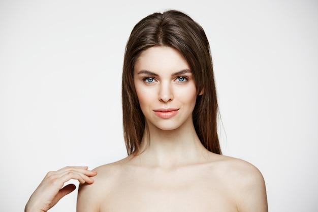 Nackte junge schöne frau mit natürlichem make-up lächelnd. kosmetologie und spa. gesichtsbehandlung.