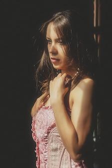 Nackte junge sexy frau im rosa korsett am riesigen antiken fenster. nettes hübsches mädchen, das emotionen mit unterwäsche aufwirft und zeigt. nackte dame im retro-stil fotoshooting. inhalte für reife nacktheit mit nacktem körper