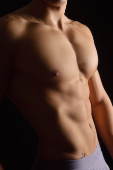 Nackte karosserie eines mannes auf schwarzem hintergrund