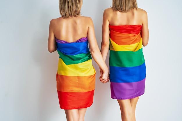 Nackte mädchenpaare, die lgbt-flagge tragen. foto in hoher qualität