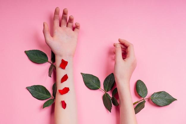 Nackte maniküre. natürliche schönheitsmädchenhände, handkosmetik mit blumenextrakt, produkt. modefrauenhand mit blume und blättern, rosafarbener hintergrundstudioschuß der kräuterhautpflege.
