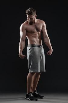 Nackte muskulöse mannaufstellung in voller länge. isolierter dunkler hintergrund