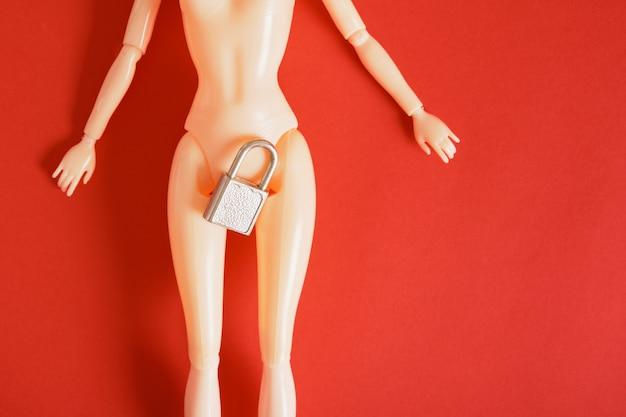 Nackte puppe auf rotem hintergrund, metallschloss zwischen den beinen der puppe, vorhängeschloss an den hüften, sexualerziehungskonzept