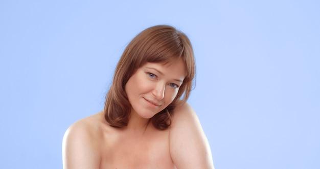Nackte sexy frau mit ausdrucksstarkem sinnlichem blickporträt eines reifen kaukasischen models auf blauer haut und ...