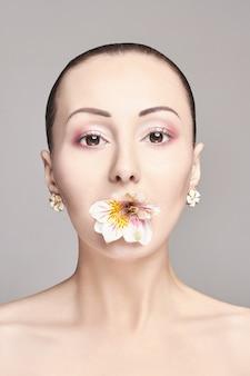 Nackter asiatischer attraktiver brunette mit blume
