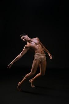 Nackter athletischer mann, der hand steht und ausdehnt