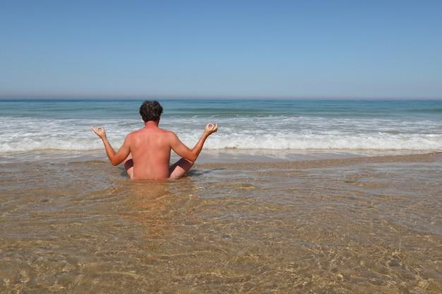 Nackter auf wasserstrand machen yoga in der hinteren ansicht am sommertag