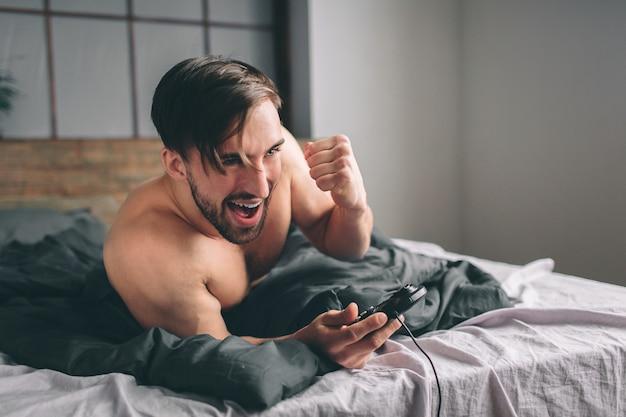 Nackter bärtiger dunkelhaariger mann, der spaß hat, videospiele online unter verwendung des steuerknüppels zu spielen