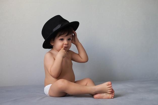 Nackter kleinkindjunge, der einen schwarzen hut trägt und auf einem grauen neutralen hintergrund sitzt und einen finger in seinem mund hält.