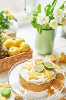 Nackter kuchen mit zitronen und limetten, früchten und weißen tulpen