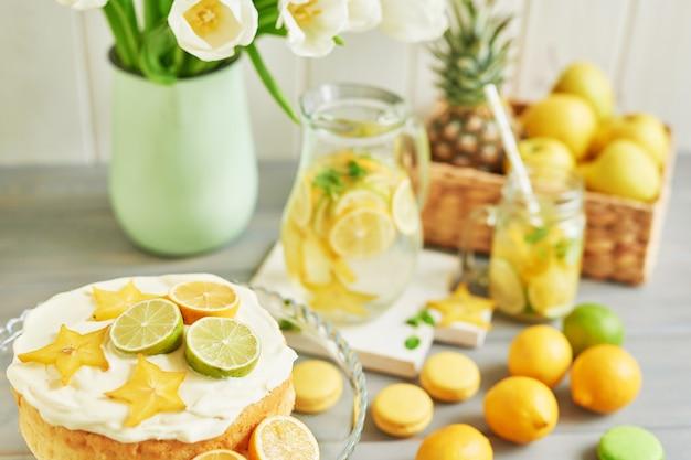 Nackter kuchen mit zitronen und limetten, limonade, früchten, süßen macarons und tulpenblüten