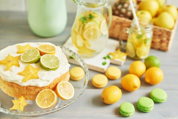 Nackter kuchen mit zitronen und limetten, limonade, früchten und süßen macarons